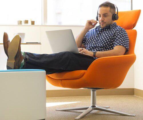 man-wearing-headphones-sitting-on-orange-padded-chair-while-1251841